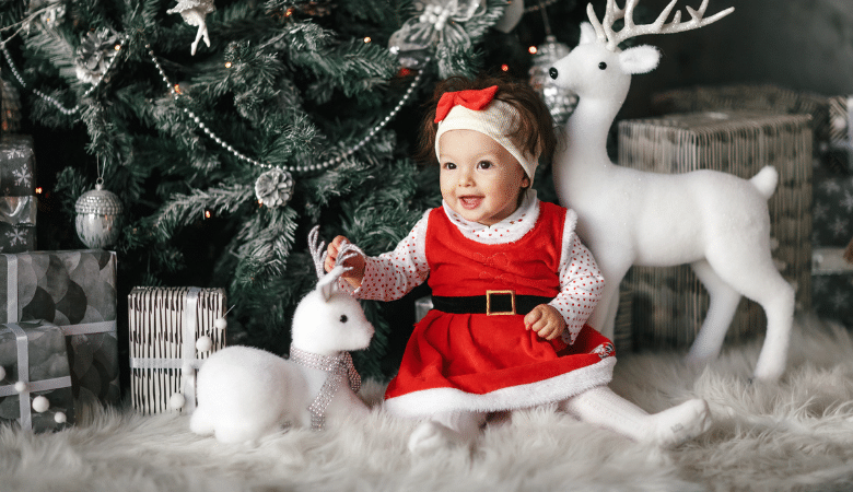 Baby celebrating first Christmas in cute Santa outfit sitting and smiling in front of Christmas tree